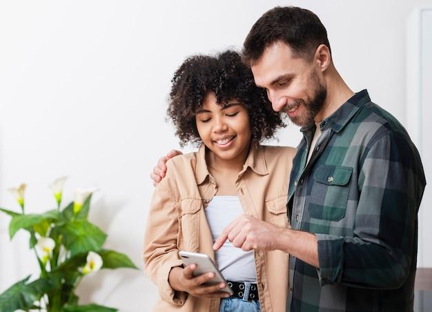 電話で見ている若い人たちの笑顔 無料写真