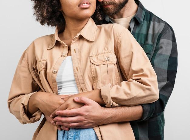 アフリカ系アメリカ人の女性を抱きしめる男の手 無料写真