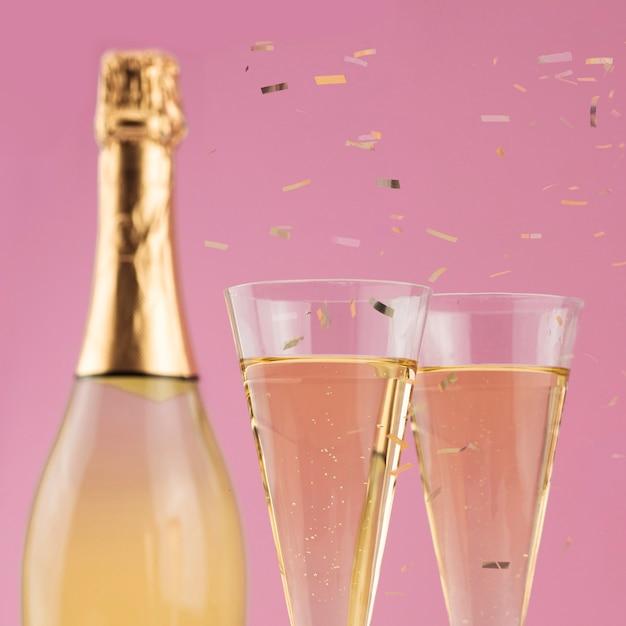 Крупный план бутылки шампанского с бокалами и конфетти Бесплатные Фотографии