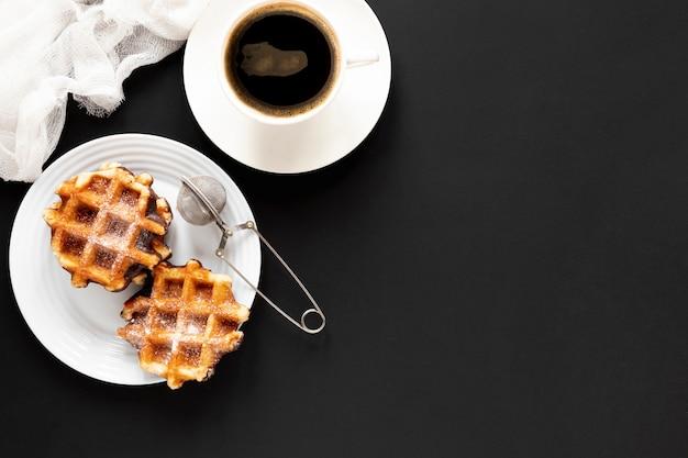 ワッフルと黒いテーブルの上のコーヒー 無料写真