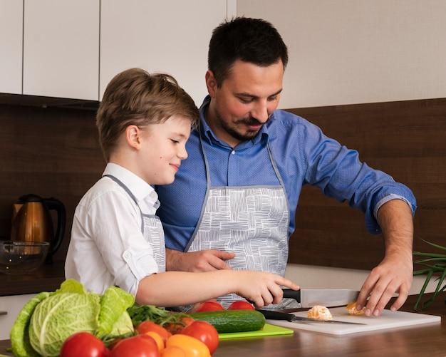 野菜をカットする息子を教えるサイドビュー父 無料写真