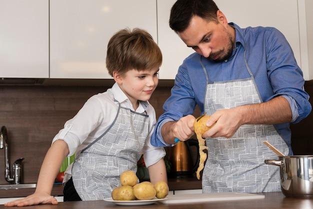 ローアングルの息子とパパがジャガイモを掃除 無料写真