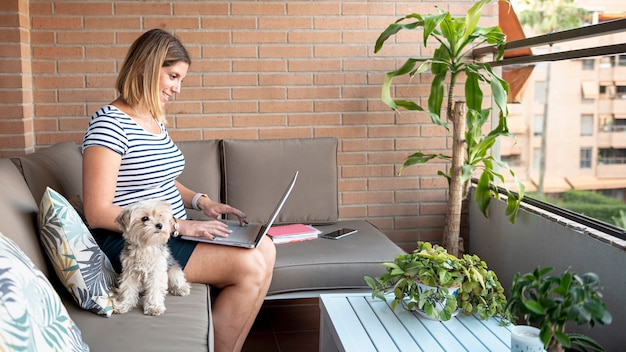 Средний снимок беременной женщины с ноутбуком и домашним животным Бесплатные Фотографии