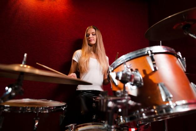 Низкий вид девушка играет на барабанах Бесплатные Фотографии