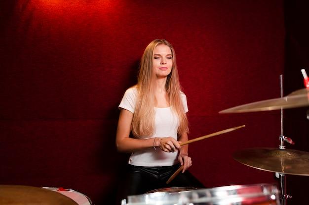Вид спереди сбоку девушка играет на барабанах Бесплатные Фотографии