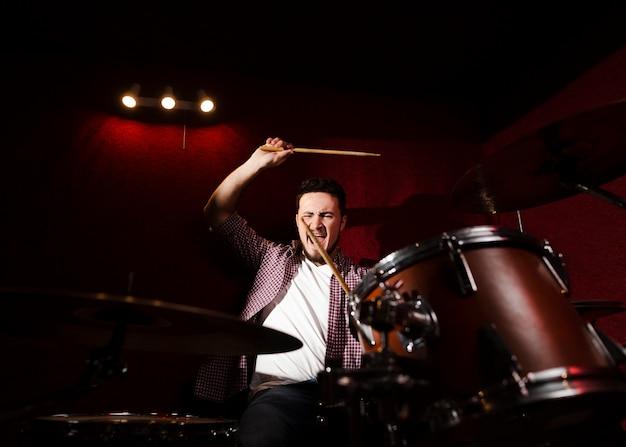 ドラムを演奏し、ドラムスティックでなでる男 無料写真