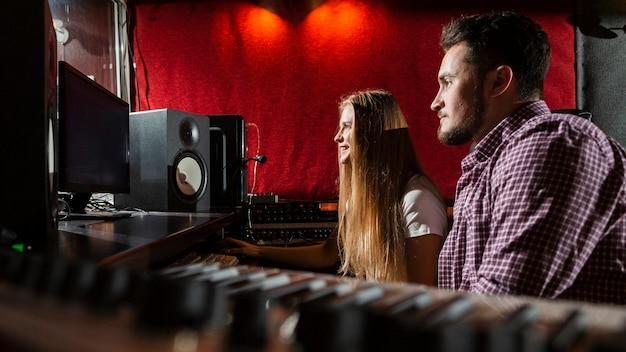 Боком пара смотрит на экраны в студии Бесплатные Фотографии