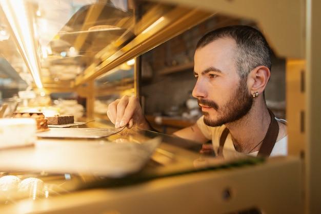 男性労働者がコーヒーショップの製品をチェック 無料写真