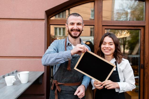フレームを保持しているスマイリーコーヒーショップの所有者 無料写真