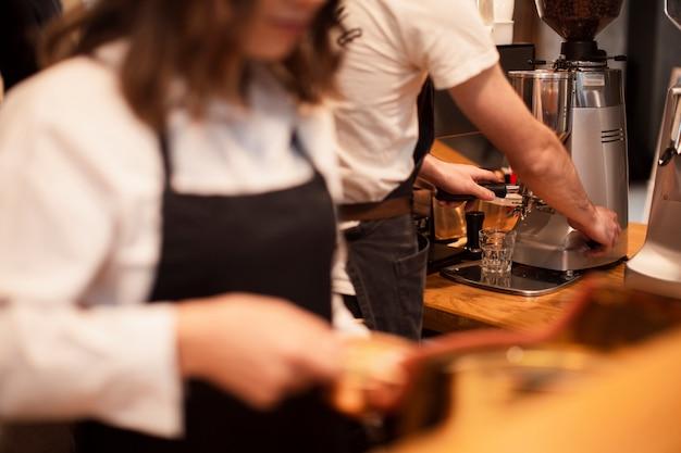 コーヒーマシンで働くコーヒーショップの従業員 無料写真