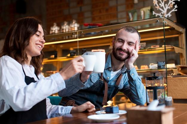 Пара в фартуках с кофе в магазине Бесплатные Фотографии