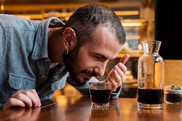一杯のコーヒーの臭いがする男のクローズアップ 無料写真