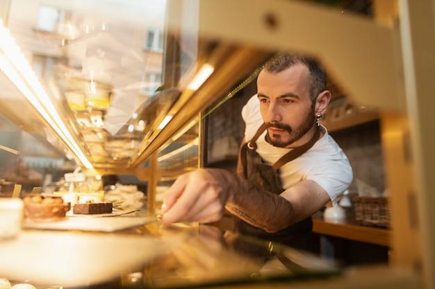 ディスプレイにクッキーを配置するエプロンの男 無料写真
