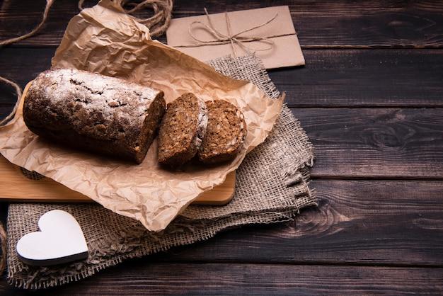 Высокий угол торта и ломтики на пергаментной бумаге Бесплатные Фотографии