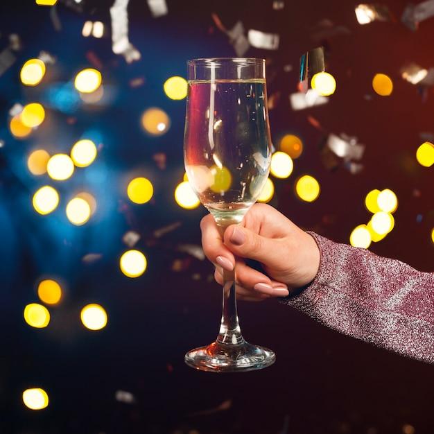 Рука с бокалом шампанского с конфетти и эффектом боке Бесплатные Фотографии