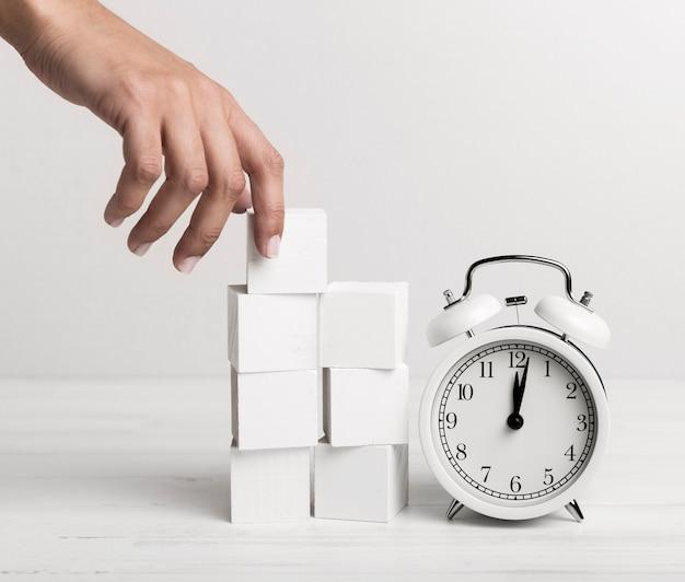Рука ставит белые кубики рядом с часами Бесплатные Фотографии