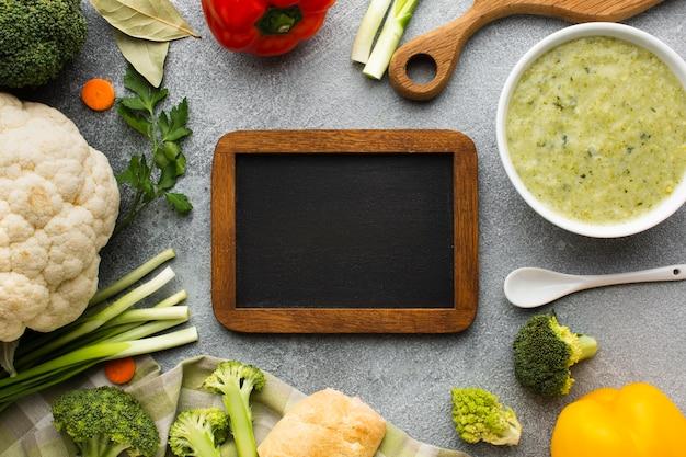 フラットレイアウトブロッコリービスクと野菜と空白の黒板 無料写真