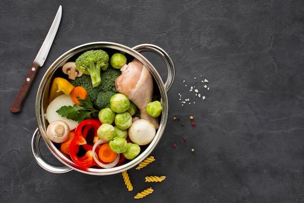 コピースペースで鍋に野菜と鶏肉のドラムスティックのミックス 無料写真