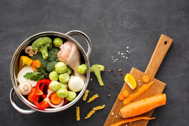 まな板の上のニンジンと鍋に野菜と鶏肉のドラムスティックのミックス 無料写真