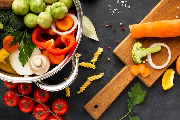 まな板の上のニンジンと鍋に野菜とチキンドラムスティックのフラットレイアウトミックス 無料写真