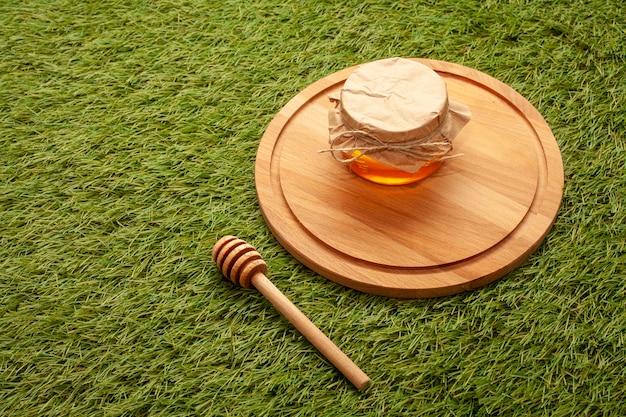 木の板に蜂蜜の瓶をクローズアップ 無料写真