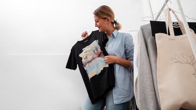 Женщина держит футболку и улыбается Бесплатные Фотографии