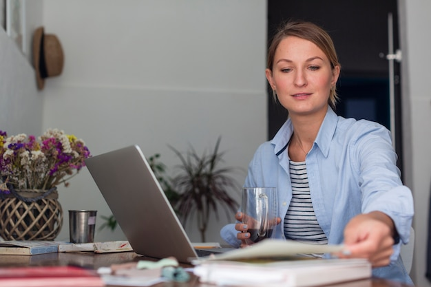 マグカップを押しながら働く女性 無料写真