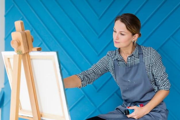 Художник работает над росписью в фартуке Бесплатные Фотографии