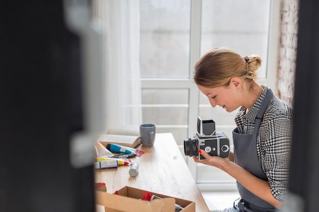 デスクでカメラを保持している女性の側面図 無料写真