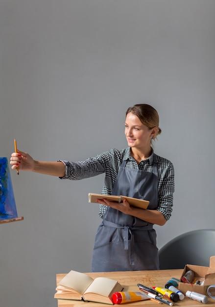 エプロンで鉛筆を保持している女性の正面図 無料写真