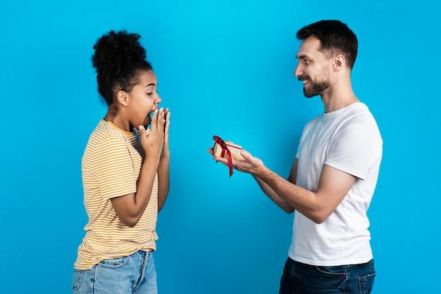 Мужчина предлагает женщине подарочную коробку Бесплатные Фотографии