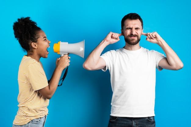 メガホンを通して男に叫んでいる女性 無料写真