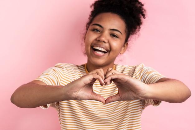 Улыбается женщина, делая форму сердца с руками Бесплатные Фотографии