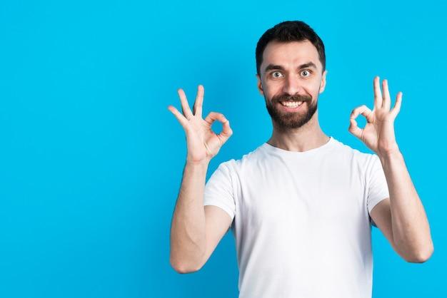 Человек улыбается и позирует, держа хорошо знаком Бесплатные Фотографии