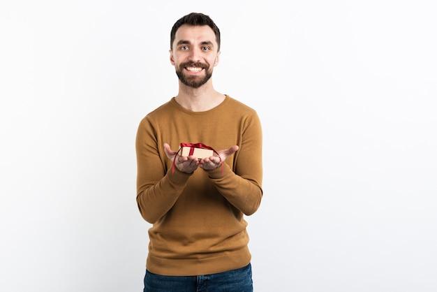 Улыбающийся человек, предлагая подарок Бесплатные Фотографии
