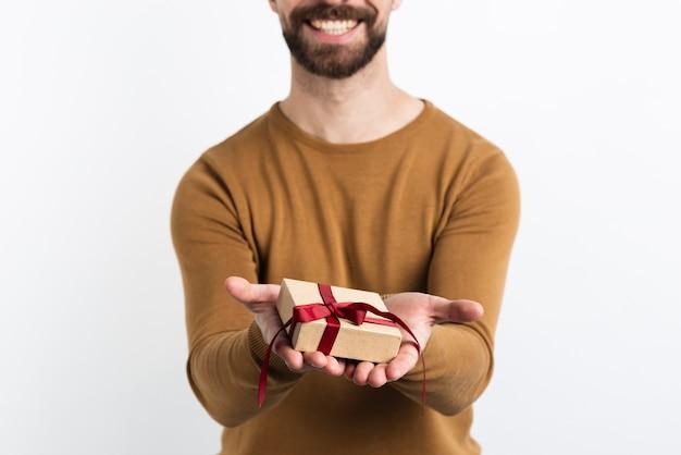 Крупный план человека, предлагающего подарок Бесплатные Фотографии