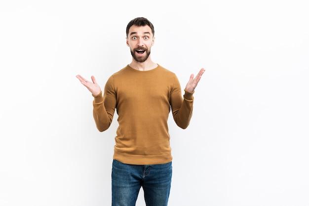 Удивленный мужчина позирует с поднятыми руками Бесплатные Фотографии