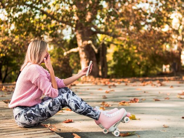 Женщина в роликовых коньках смеется над смартфон Бесплатные Фотографии
