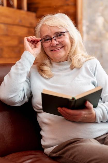 スマイリー年配の女性が自宅で読書 無料写真