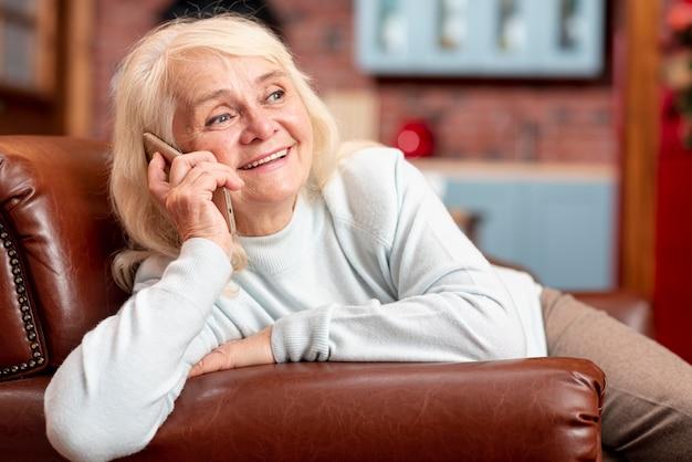 電話で話しているソファの上のスマイリーの女性 無料写真