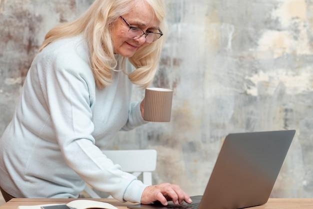 Высокий угол старшая женщина, работающая из дома Бесплатные Фотографии
