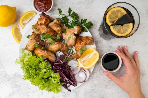 Вид сверху вкусные куриные крылышки с салатом Бесплатные Фотографии