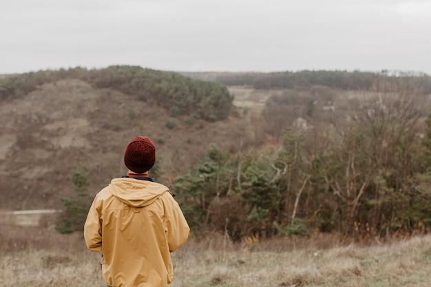Вид сзади путешественник смотрит на пейзаж Бесплатные Фотографии
