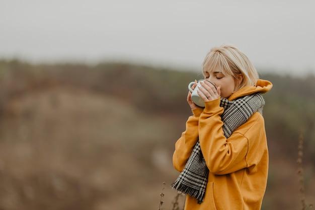 冬の旅行でお茶を飲む若い女性 無料写真