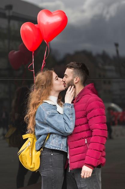 カップルがキスのミディアムショット 無料写真