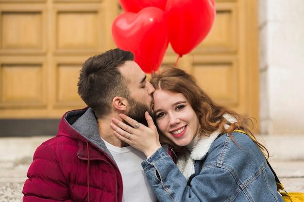 ガールフレンドにキスをする男性のミディアムショット 無料写真