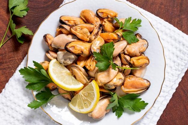 Макро вкусные мидии с петрушкой на тарелке Бесплатные Фотографии
