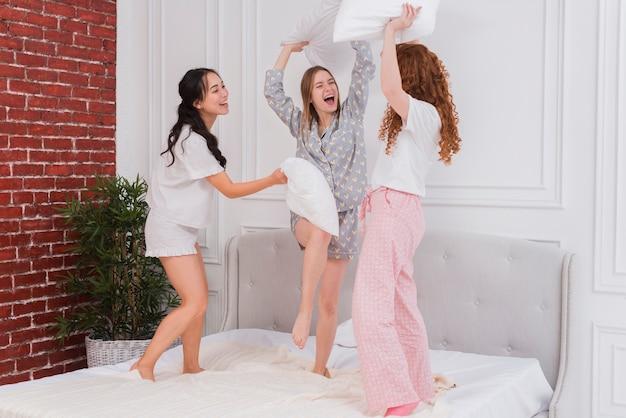 枕と戦う若いガールフレンド 無料写真
