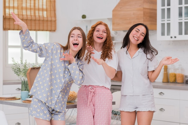 Подруги поют на пижамной вечеринке Бесплатные Фотографии
