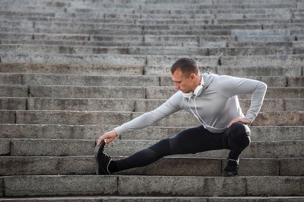 若い男が階段でウォーミングアップ 無料写真